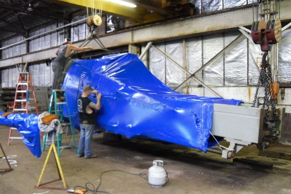 Unlimited Shrinkwrap hoists a large object for an industrial shrink wrap project.