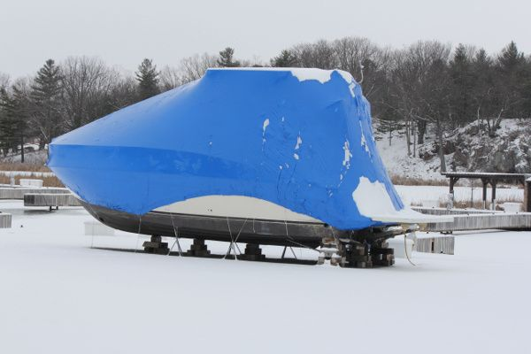 Photo of a boat with shrink wrap on it in winter.
