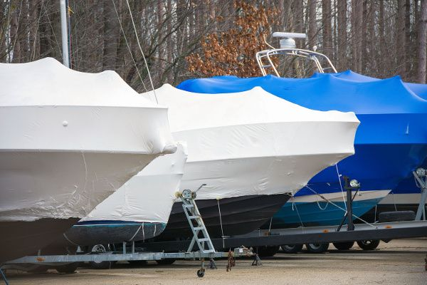 Photo of a row of boats with boat shrink wrap on them.