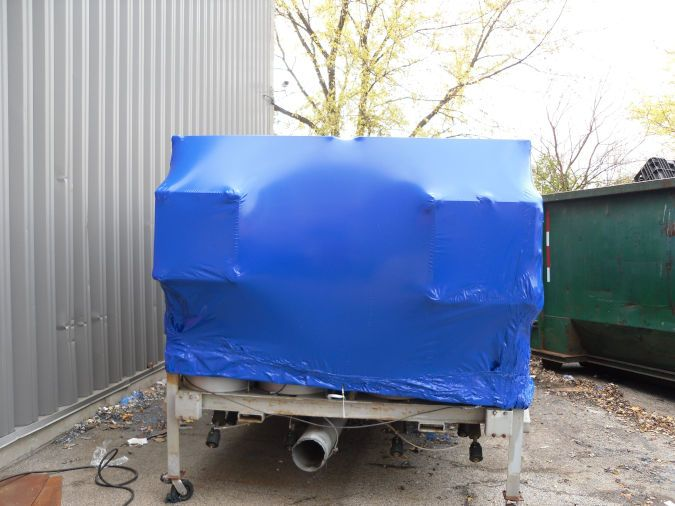 Equipment that has been shrink wrapped for storage sits on a trailer outside.